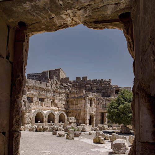 Blick durch einen steinernen durchgang in einen weitläufigen Innenhof mit antiken Ruinen