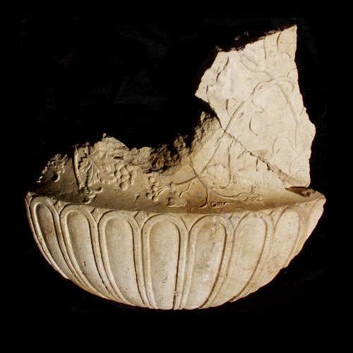 Fragment eines antiken Steingefäßes vor schwarzem Hintergrund