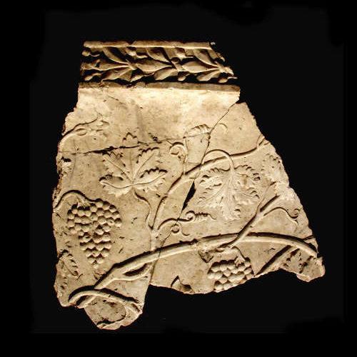 Fragment eines antiken Steingefäßes mit Weinranken und Zierborte aus Baalbek, Libanon vor schwarzem Hintergrund