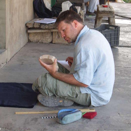 Autor und Archäologe Holger Wienholz, auf dem Boden sitzend, betrachtet ein Fragment eines römischen Steingefäßes