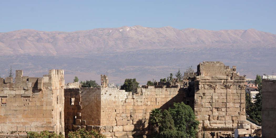 Blick über antike Ruinen, dahinter ein Gebirgszug.