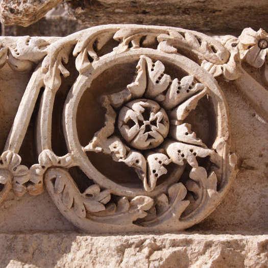 sandfarbenes Steinornament mit umrankter Blüte, leicht beschädigt