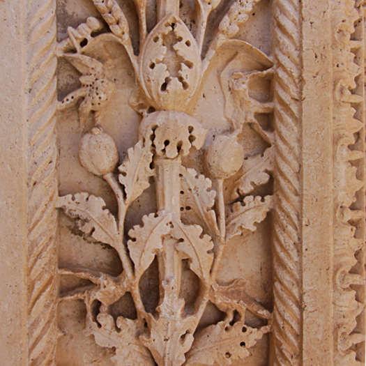 Sandfarbene Steinornamente mit Ranken, Blüten und Blättern.