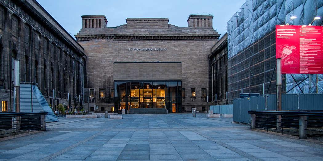 Blick auf den Vorplatz des Pergamonmuseum in der Dämmerung, im Hintergrund das Museum.