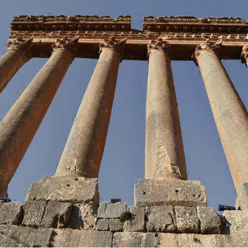 Blick von unten auf mächtige antike Steinsäulen, dahinter blauer Himmel
